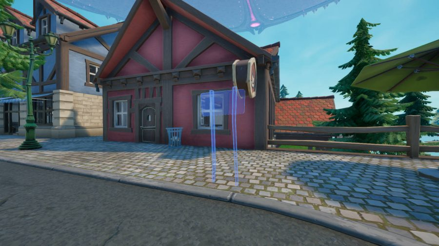 A light blue outline of a sign outside of a pink cottage in Fortnite
