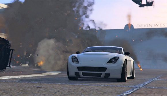 A Grand Theft Auto V white sports car speed down a street past a car wreck on fire