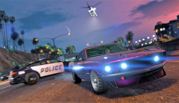 A GTA Online blue car speeds up a road past a police car and helicopter