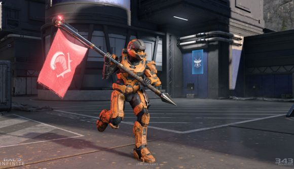 A Spartan in orange armour carries a red flag in Halo Infinite multiplayer.