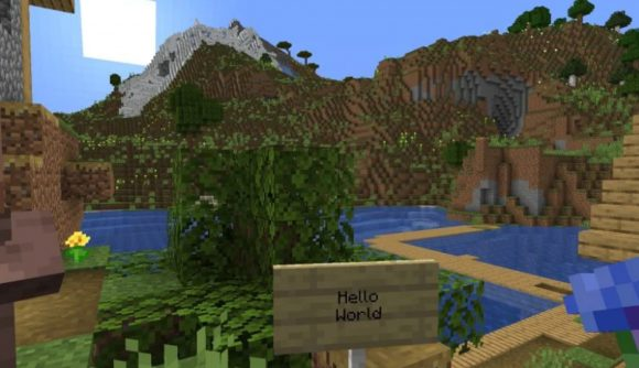 A Minecraft sign says 'hello world' in front of a river and mountain range