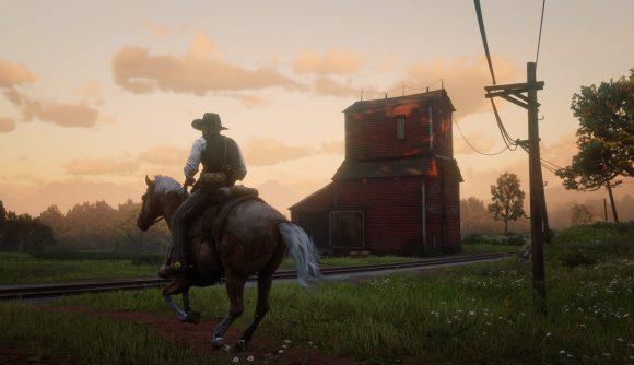 Arthur Morgan rides by a red barn near sundown in Red Dead Redemption 2