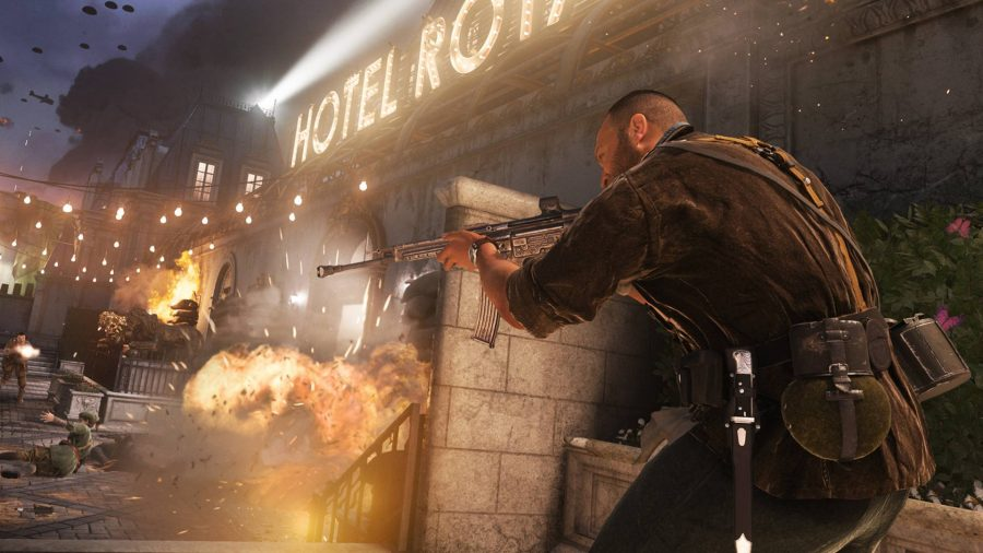 A man holding a gun and an explosion at the hotel behind him