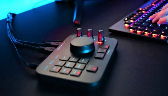 Photo of Audio Radar accessibility device control panel sitting on black desk with gaming keyboard on left