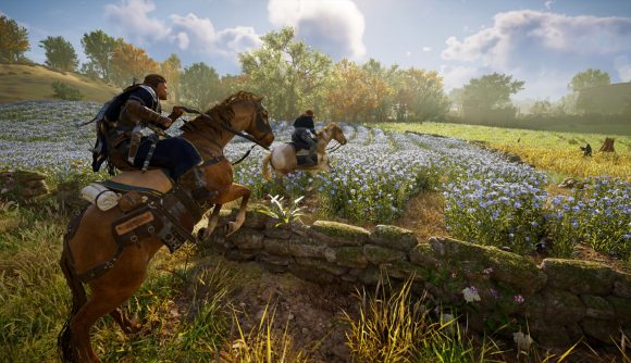Eivor and a companion ride on horseback through a sunny field of flowers in Assassin's Creed Valhalla.