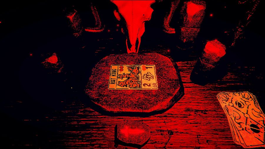A red and black table with a ram skull overlooking it, with a 'Rat King' tarot card in the table's centre