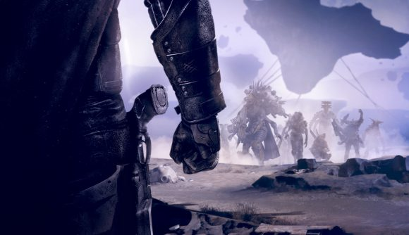 A closeup of a fist and a holstered gun as enemies approach in Destiny 2