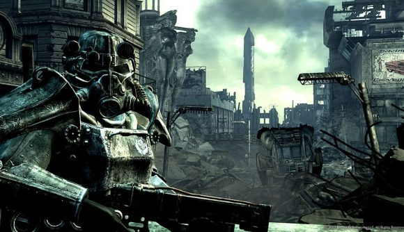 A figure in power armour looms in the foreground in front of the ruins of Washington, DC in Fallout 3.