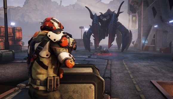 An armoured soldier faces off against a towering crab alien in Phoenix Point.