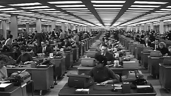 An endless row of office workers at grim desks.
