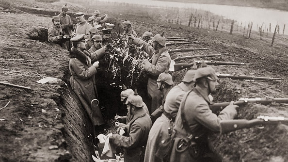 Black and white photo of German troops in a World War One trench decorating a small Christmas tree while others keep their rifles trained toward enemy lines.