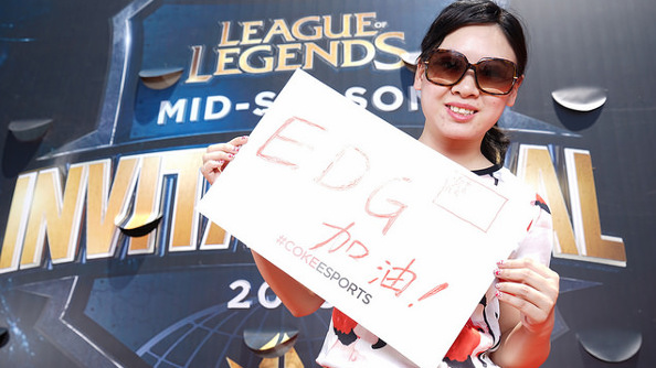 A Chinese woman wearing large black sunglasses holds a hand-drawn Edward Gaming sign