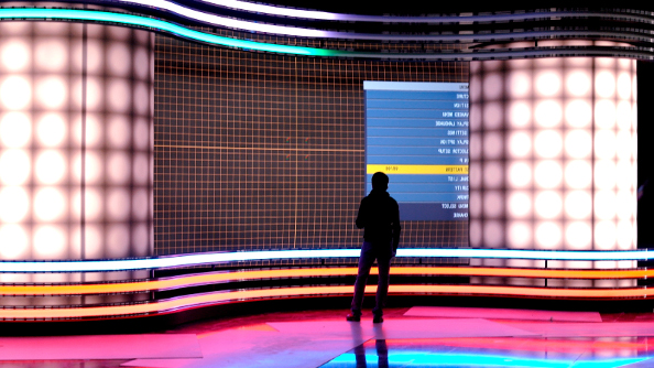 A lone figure on a glossy stage stands in silhouette against the neon backdrop while a test screen menu is displayed on the screen.