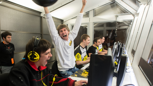 A white-shirted, blonde player celebrates his victory at The International, thrusting a victorious fist into the air while his teammates look on.