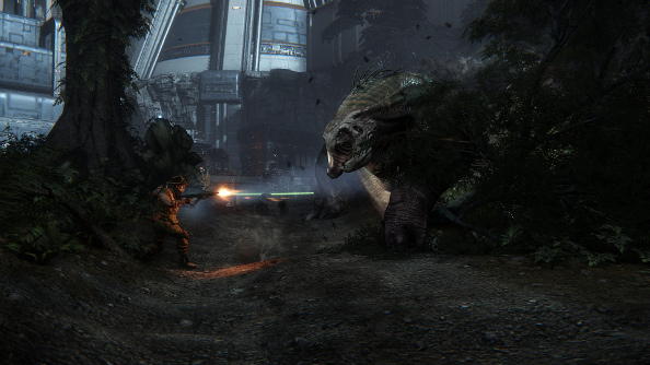 A lone hunter in a bush hat blasts a giant monster with a shotgun along a darkened jungle trail.