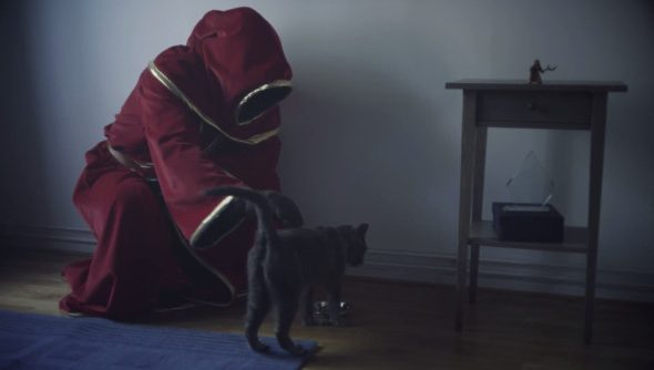 A sad wizard in a red robe strokes a gray cat in a depressing modern apartment.