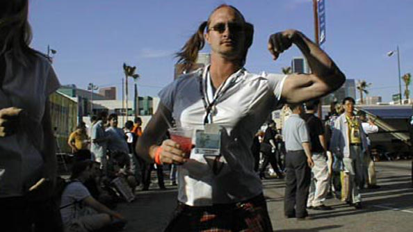 A younger Mike Wilson, wearing a schoolgirl outfit and flexing his left bicep at an old E3.