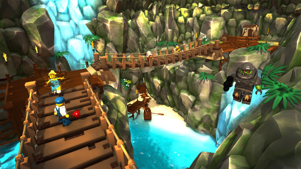 A group of LEGO characters run over a rope bridge suspended over a colorful river and waterfall in the tropics.