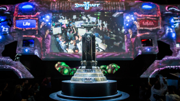 The WCS trophy waits to be claimed in the foreground while behind it the championship is played on a huge screen.