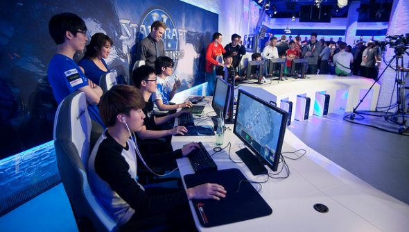 The casters and pros of North American and European StarCraft arrayed in a row around desktop PCs.