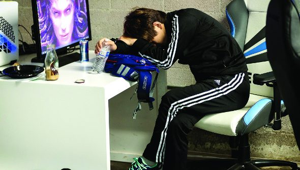 A StarCraft pro slumps in his chair next to a monitor after losing his series in WCS Season 3 America.