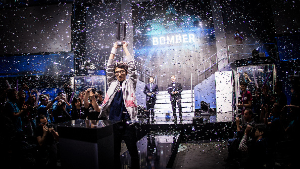 Bomber, a thin Korean pro player wearing a white zip-up team jacket, holds aloft the season 2 trophy with a look of confidence as confetti falls around him.