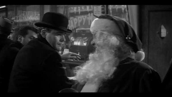 """A still from """"The Apartment"""" with Jack Lemmon. In black and white, Lemmon glowers at a drunk Santa in a seedy bar."""