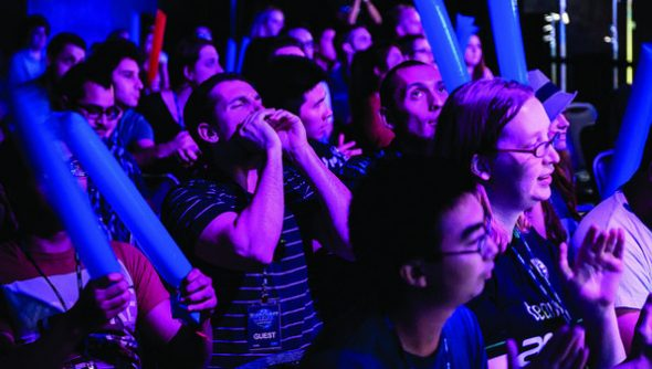 A crowd of nerds illuminated by purple LEDs watch the WCS America Finals, cheering and screaming.