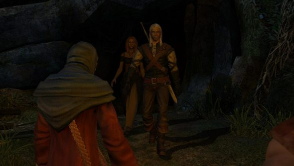 The silver-haired Geralt strides down a cave tunnel entrance to face a medieval mob lit by torchlight.